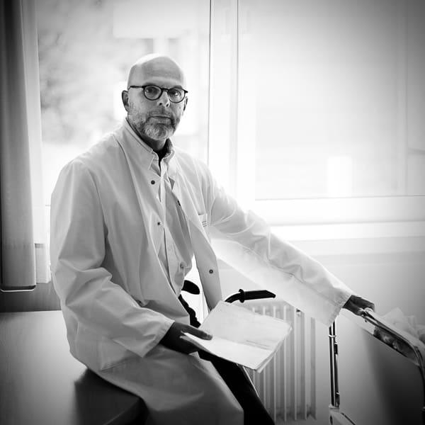 Dr. Johannes Kuchta im Arztkittel am Krankenbett